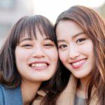 笑顔の20代前半の女性2人が寄り添っている