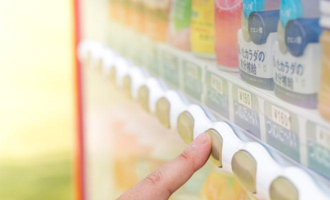 自動販売機のボタンを押そうとしている人