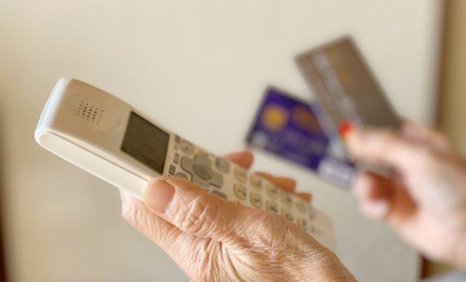 電話機とクレジットカードを持つ高齢者の手